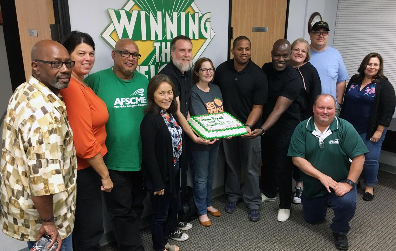 Local 1 leaders and Council 57 board members celebrate merger with a cake