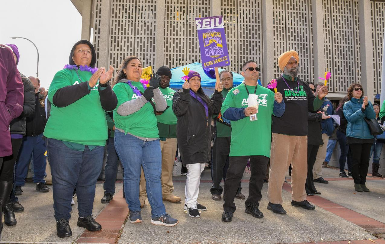 AFSCME Local 829 members and SEIU members listen to speakers at the Together We Rise rally in San Mateo County.